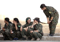 Syrian Democratic Forces female fighters sit together on a curb in the city of Hasaka