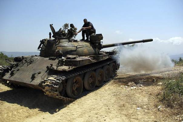 Rebel fighters are seen on a tank during what they said an offensive against forces loyal to Syria's President Bashar al-Assad who are positioned around the Armenian Christian town of Kasab May 26, 2014. REUTERS/Alaa Khweled
