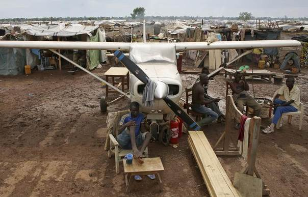 Internally displaced men sit under a plane in an IDP camp located at Bangui International Airport, April 10, 2014. REUTERS/Goran Tomasevic