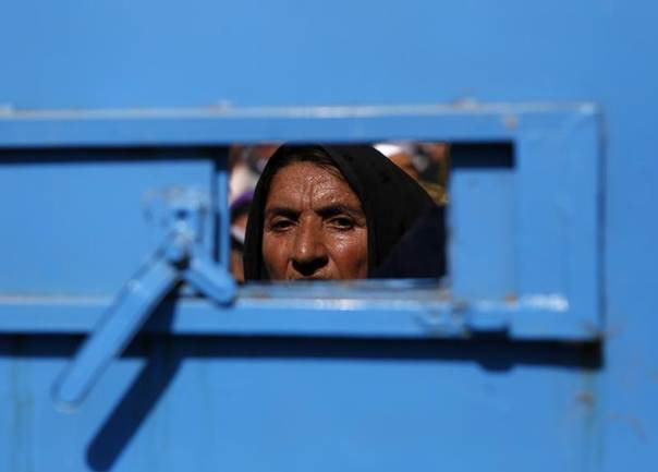 An Afghan woman waits to receive aid as she stands behind the door of the Afghanistan Chamber of Commerce and Industries during Ramadan in Kabul, Aug. 1, 2013. REUTERS/Mohammad Ismail