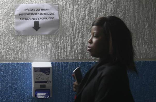 A woman walks past a antiseptic dispenser, placed to be used as a preventive measure against Ebola, at the health minister's office in Abidjan August 11, 2014. REUTERS/Luc Gnago