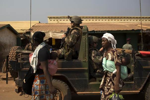 Women walk past a vehicle carrying French peacekeeping troops in a Muslim neighbourhood in the capital Bangui January 17, 2014. REUTERS/Siegfried Modola