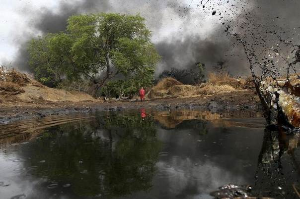 In this 2011 file photo, a man walks as crude oil spills from a pipeline in Dadabili, Niger state REUTERS/Afolabi Sotunde