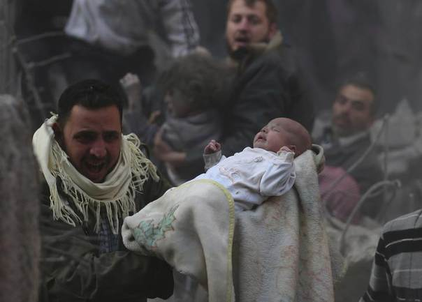 A man carries a baby who survived what activists say was an airstrike by government forces in the Duma neighbourhood of Damascus. Picture January 7, 2014, REUTERS/Bassam Khabieh