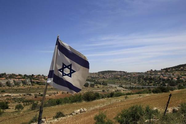 An Israeli flag waves on a hill near the West Bank Jewish settlements of Elazar (rear L) and Efrat (rear R), in the Etzion settlement bloc near Bethlehem May 22, 2011. REUTERS/Ronen Zvulun