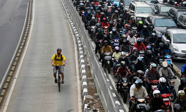 In a 2011 file photo, a man rides a bicycle in a bus lane next to a morning rush hour traffic jam in Jakarta. REUTERS/Supri