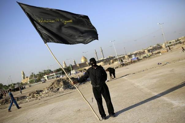 A member of the Mehdi Army loyal to Shi'ite cleric Moqtada al-Sadr holds a black flag that reads,