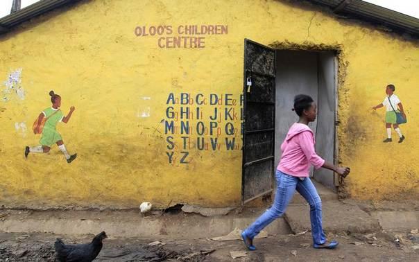 A girl walks past a school in Nairobi's Kibera slum May 9, 2014. REUTERS/Noor Khamis