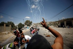 Palestinian protesters take cover during clashes with Israeli troops