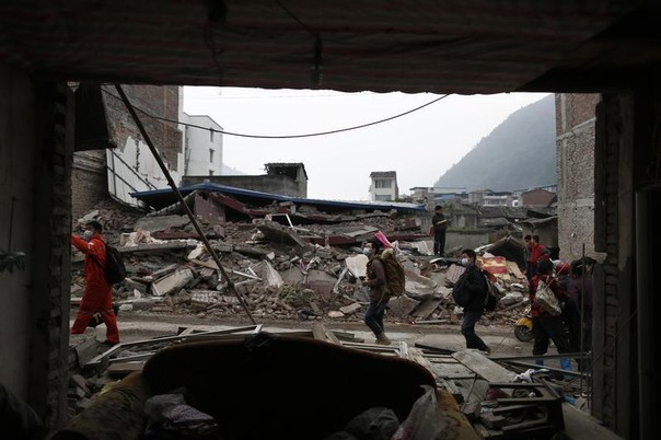 People walk past a building damaged in an earthquake
