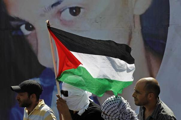 Palestinians look on as they stand in front of a poster depicting 16-year-old Mohammed Abu Khudair during his funeral in Shuafat, an Arab suburb of Jerusalem July 4, 2014. REUTERS/Finbarr O'Reilly