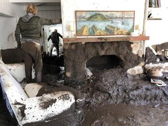 Family members inspect the inside of a home covered in mud following the mudslides in Montecito, California, U.S.