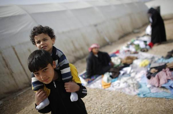 Syrian refugee boys stroll at a refugee camp in Nizip in Gaziantep province, near the Turkish-Syrian border March 17, 2014. Picture taken March 17, 2014. REUTERS/Murad Sezer