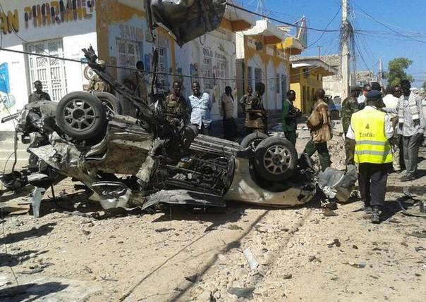 People mill around the mangled wreckage of a car destroyed in a blast along a street in the coastal city of Bosasso December 5, 2013. REUTERS/Abdiqani Hassan
