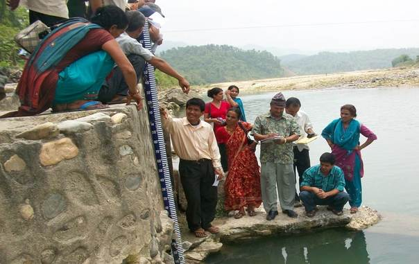 A local community on the Rapti River of west Nepal checks the depth of water in the river during training on early warning alerts. Photo: Practical Action