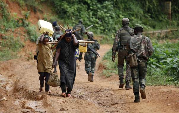 Democratic Republic of Congo military personnel walk past women as they patrol near Beni in North-Kivu province, Democratic Republic of Congo, December 31, 2013. REUTERS/Kenny Katombe
