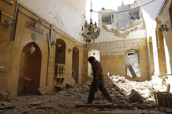 A man walks inside a mosque damaged by, according to activists, a barrel bomb thrown by forces loyal to Syria's president Bashar Al-Assad in Old Aleppo May 1, 2014. REUTERS/Jalal Al-Mamo