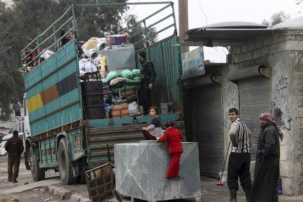 Residents put their belongings on a lorry at an area damaged by what activists said was an air strike by forces loyal to Syria's President Bashar al-Assad, in Salehin neighbourhood in Aleppo January 25, 2014. REUTERS/Hosam Katan