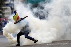 A demonstrator clashes with riot security forces during a rally against Venezuela's President Nicolas Maduro's government in Caracas