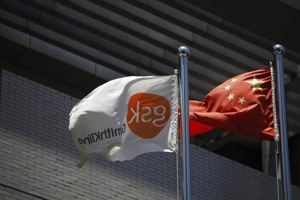 A flag bearing the logo of GlaxoSmithKline (GSK) flutters next to a Chinese flag outside a GlaxoSmithKline building in Shanghai. Picture taken July 12, 2013. REUTERS/Aly Song