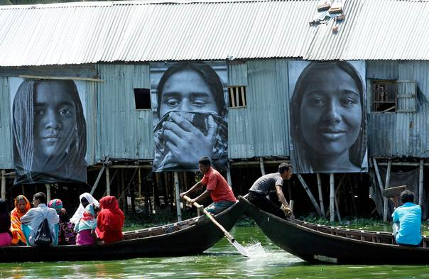 Boats carrying slum dwellers pass photographs of garment workers taken by students of the Counter Foto photography department in Dhaka, on Sept. 13, 2013. The photographs of garment workers are part of the