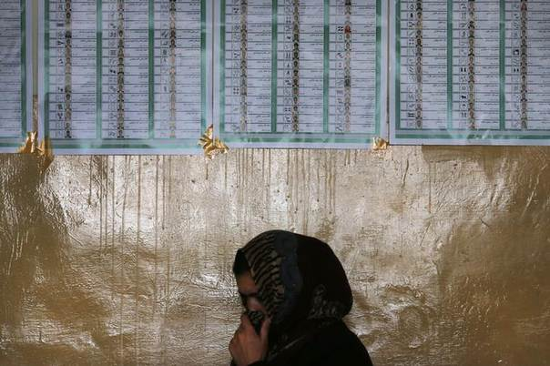An election official pauses under a list of candidates taped to the wall of a polling station in Kabul April 5, 2014. REUTERS/Tim Wimborne