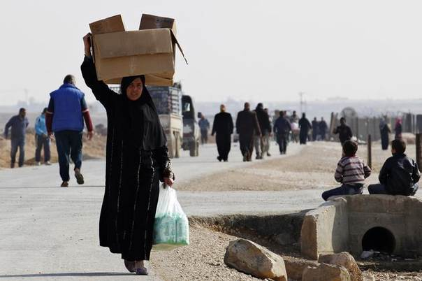 DATE IMPORTED:December 31, 2013A Syrian refugee carries boxes of aid at Al-Zaatri refugee camp in the Jordanian city of Mafraq, near the border with Syria December 31, 2013. REUTERS/Muhammad Hamed