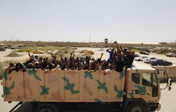 Volunteers, who have joined the Iraqi army to fight against the predominantly Sunni militants from the radical Islamic State of Iraq and the Levant (ISIL) who have taken over Mosul and other northern provinces, wave from a truck in Baghdad, June 16, 2014. REUTERS/Ahmed Saad