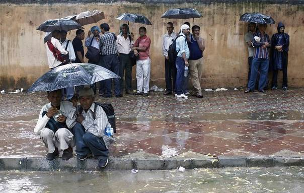 People take shelter under umbrellas during a rain shower in New Delhi, Aug. 5, 2013. REUTERS/Anindito Mukherjee