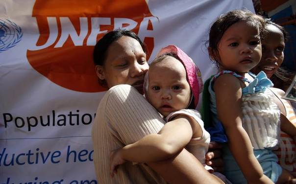 Women carry their children during a medical mission for flood victims, by the United Nations Population Fund (UNFPA), in Tondo, Manila August 30, 2013. REUTERS/Erik De Castro