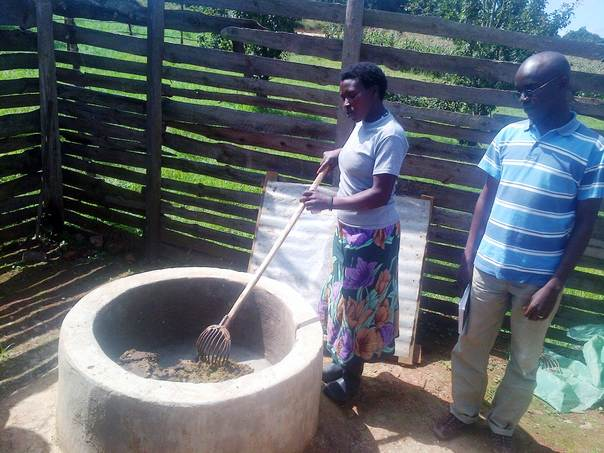 Aloycia Mndenye prepares cow dung before discharging it into a biogas digester, with Abdallah Musa, a researcher from Sokoine University of Agriculture, looking on. THOMSON REUTERS FOUNDATION/Kizito Makoye