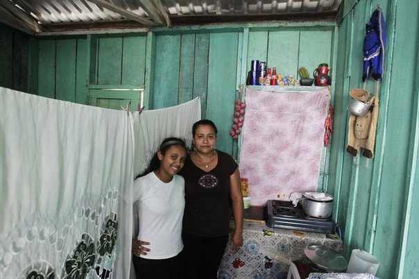 Susana Maria Cardona, 33, and her daughter Alejandra Ruby Cardona, 12, pose for a photograph inside their home in Tegucigalpa, Honduras February 20, 2014.   Susana Maria, who is a housewife, finished school at 17. Her ambition was to become a lawyer and now she hopes that her daughter will become a doctor.  Alejandra Ruby will finish education in 11 years and hopes to be an agronomist.
