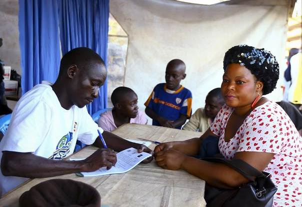 A medical officer takes down a woman's details before she takes an HIV/AIDS test at a mobile testing unit in Ndeeba, a suburb of Uganda's capital Kampala. Picture May 16, 2014, REUTERS/Edward Echwalu