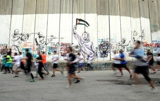 Participants run past the Israeli barrier during a marathon