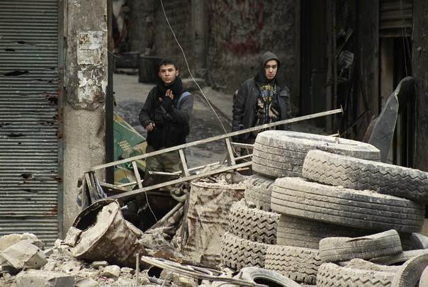 Free Syrian Army fighters gesture as they stand behind tyres and barricades near Aleppo's historic citadel, which is controlled by forces loyal to Syria's President Bashar al-Assad February 10, 2014. REUTERS/Ammar Abdullah