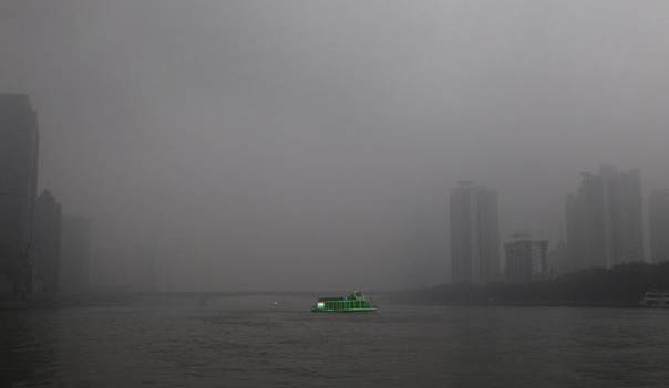 A tourist boat, decorated with green lights, travels on the Pearl River amid heavy haze in Guangzhou, Guangdong province, March 3, 2014. China's environment ministry has vowed to 'harshly punish' factories REUTERS/Alex Lee
