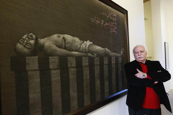 Syrian artist Youssef Abdelke stands near his artwork during an exhibition at a gallery in Beirut January 6, 2014. While activists and state journalists are out on the front line recording every shell blast and clash, silver-haired 63-year-old painter Abdelke has found his own more personal way of reporting on the hardships of fellow Syrians, using charcoal and paper.  REUTERS/Jamal Saidi