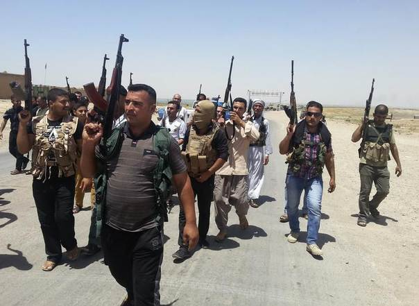 Tribal fighters and members of Iraqi security forces carry their weapons as they take part in an intensive security deployment on the outskirts of Diyala province June 14, 2014 REUTERS/Stringer