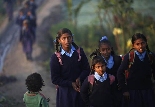 Girls make their way to school through a vegetable field in the early morning in New Delhi, Dec. 11, 2013. REUTERS/Ahmad Masood