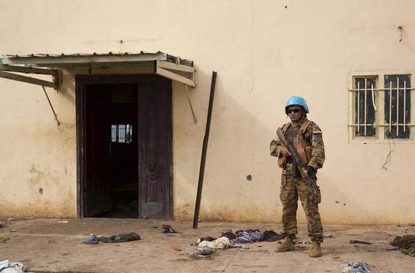 A United Nations peacekeeper stands guard near the scene where about 200 people were killed during an attack in Bentiu, Unity state of South Sudan April 20, 2014. REUTERS/Emre Rende