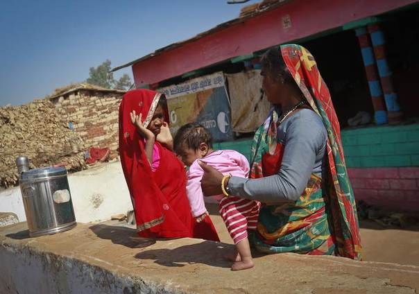 Krishna, married at 11 and now 14, speaks to a relative holding her 4-month-old baby Alok at her house in a village in India's Rajasthan state, January 21, 2013. Picture  REUTERS/Danish Siddiqui