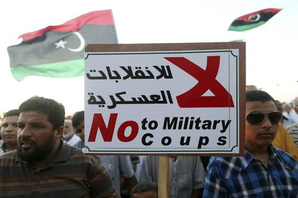 People wave Libyan national flags and hold up a sign during a demonstration against the country's parliament and in support of the coalition of fighters called the Benghazi Revolutionaries Shura Council, at Freedom Square in Benghazi August 29, 2014. REUTERS/Esam Omran Al-Fetori