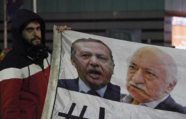 A demonstrator hold pictures of Turkey's Prime Minister Tayyip Erdogan and Turkish cleric Fethullah Gulen (R), during a protest against Turkey's ruling AK Party (AKP), demanding the resignation of Erdogan, in Istanbul December 30, 2013 REUTERS/Osman Orsal