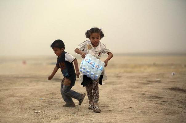 A girl, who fled from the violence in Mosul, carries a case of water at a camp on the outskirts of Arbil in Iraq's Kurdistan region, June 12, 2014. REUTERS/Stringer