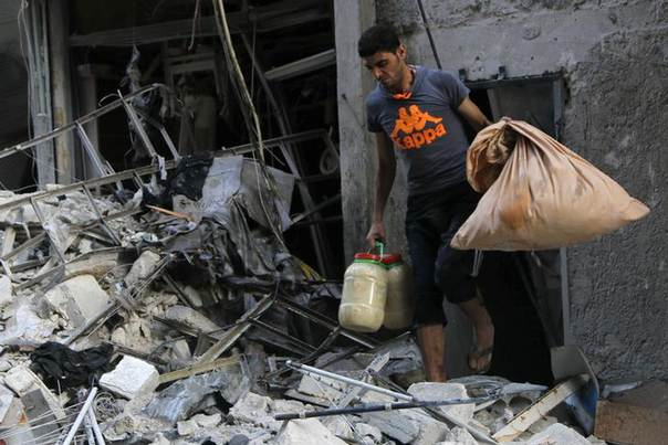 A man carries belongings as he walks among debris of a collapsed buildings at a site hit by what activists said was a barrel bomb dropped by forces loyal to Syria's President Bashar al-Assad in Aleppo's Bustan al-Qasr neighborhood May 28, 2014 REUTERS/Hosam Katan