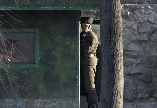 A North Korean soldier holds a gun as he stands guard at the banks of Yalu River near the North Korean town of Sinuiju, opposite the Chinese border city of Dandong, December 21, 2013. REUTERS/Jacky Chen