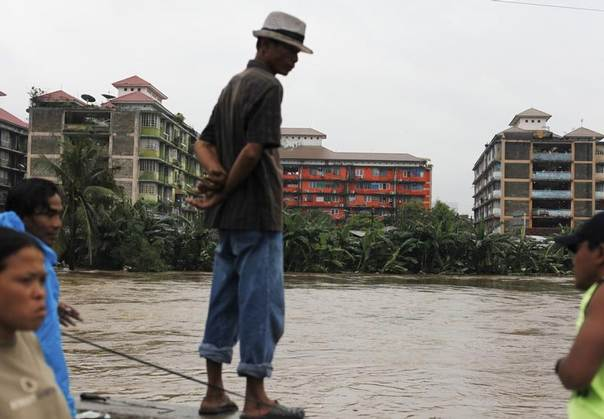 A man stands on a dam as he looks at the flood-affected Tanah Abang slum area in Jakarta, Jan. 17, 2013. REUTERS/Beawiharta