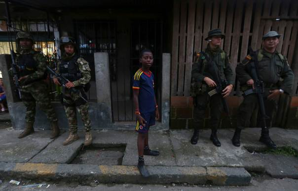 A boy stands next to Colombian Special Forces at a street in the
