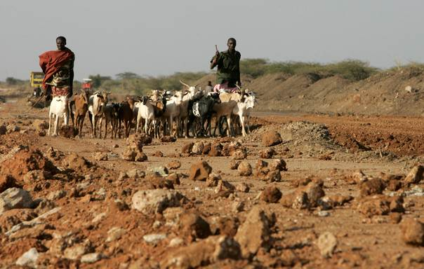 A Maasai herdsman walks with his goats past a road construction project near Isiolo town, 320 km (200 miles) north from the Kenyan capital Nairobi on July 7, 2008. REUTERS/Antony Njuguna
