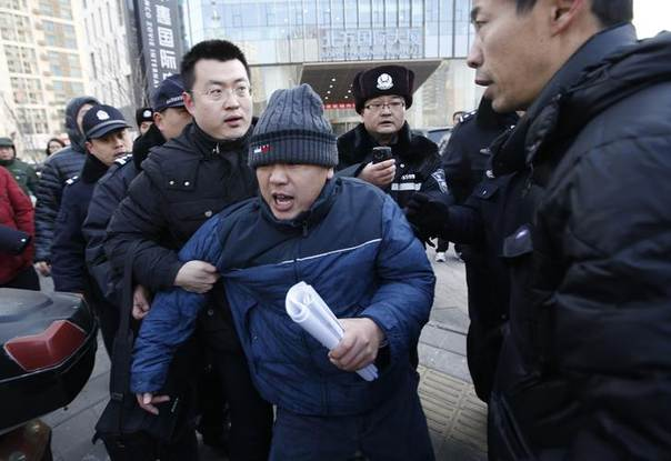 A plainclothes policeman holds onto Zhang Qingfang (C), the lawyer of Xu Zhiyong, to put him into a police car as journalists follow the lawyer after Xu's trial, near the Beijing No. 1 Intermediate People's Court in Beijing January 26, 2014. REUTERS/Kim Kyung-Hoon